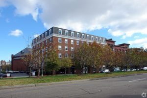 view of 5 story masonry building from across the street