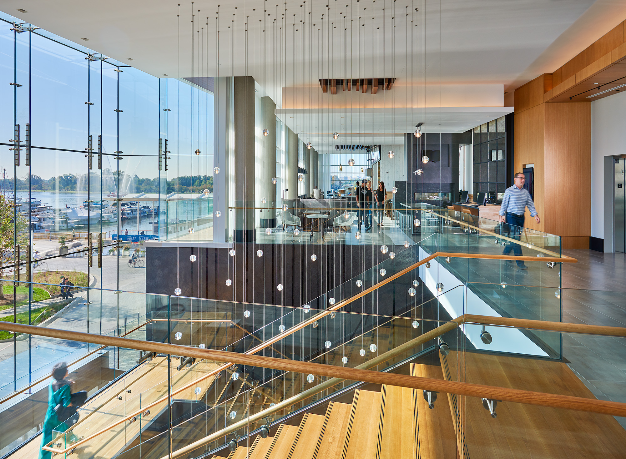 Hotel lobby with tall glass windows and wide staircase
